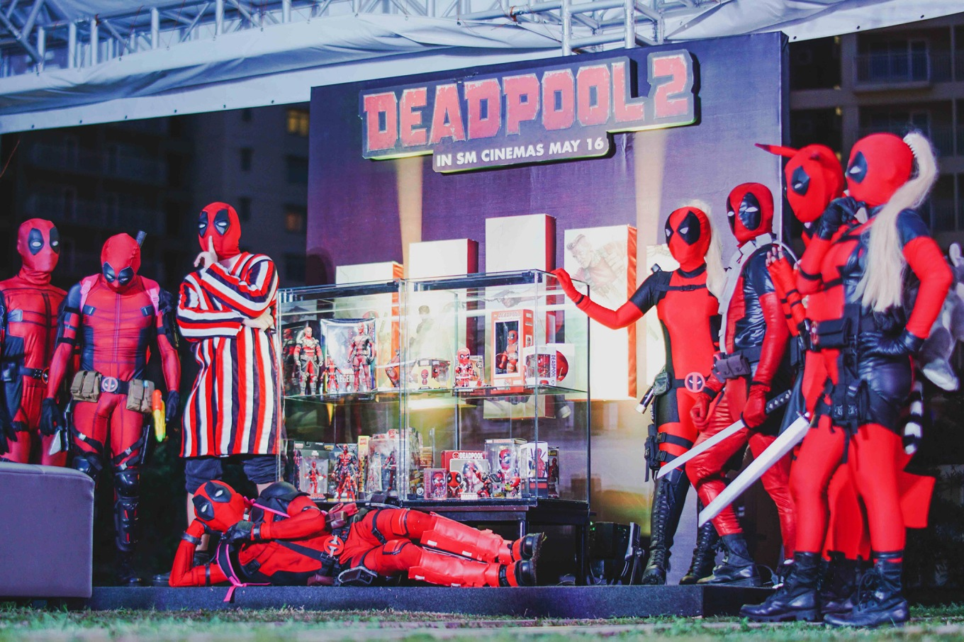 Cosplayers pose with the Deadpool character action figures