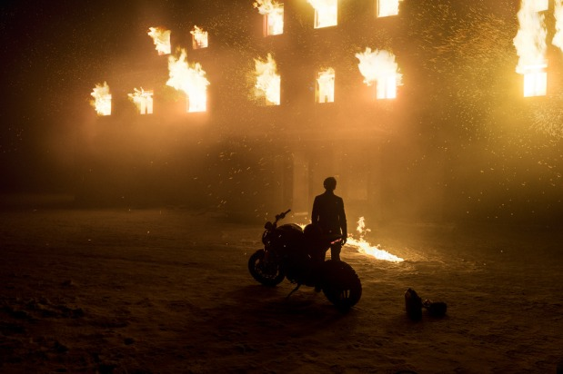 """Lisbeth Salander (Claire Foy) with her bike outside burning Brandmauer manor in Columbia Pictures' THE GIRL IN THE SPIDER'S WEB"""""""